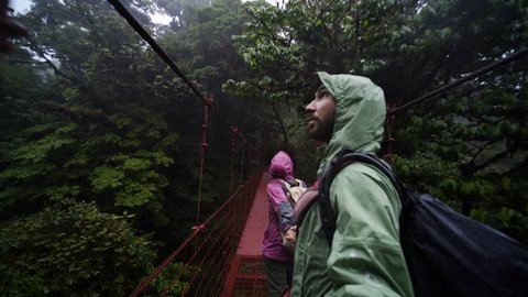Couple walking hand by hand on hanging bridge through rain forest, national park Monteverde, Costa Rica