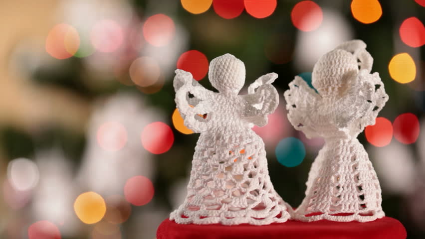 Two crocheted xmas angels decorations in front of christmas tree with blinking colorful lights - closeup with copy space