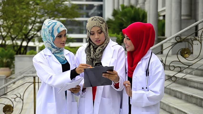 Close-up portrait of beautiful young Asian Muslim medical students looking file and smile