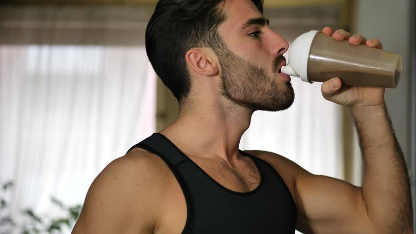 Young athletic man drinking a healthy smoothie drink or a protein shake from blender or shaker at home in kitchen