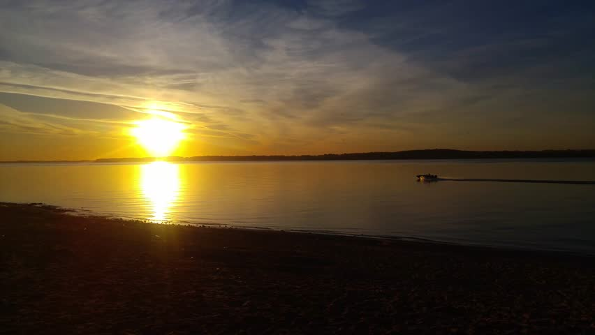 Sunset over a wide river with a sandy beach. The sun is reflected in the water, the blue beautiful sky, bright evening | Shutterstock HD Video #31846159