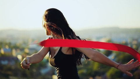 Young brunette attractive women dance rhythmic gymnastics, modern with red ribbon in black sexy dress. City sunset background.Slow motion.