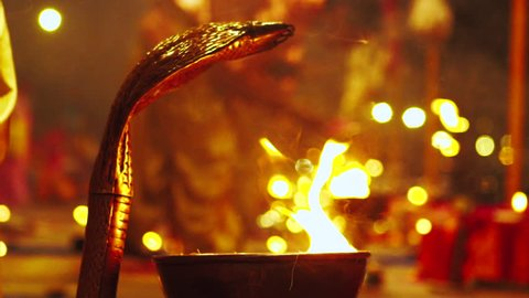 Graded & ungraded: Rose petals placed on gold religious snake head during Hindu ceremony at Ganges River celebration with candle lit prayer at night - Slow motion close up