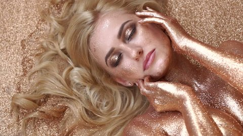 Portrait of a luxurious model girl with golden skin, hair and gold make-up, which lies on the floor on a gold background. Fashion beauty girl lying on golden glitter.