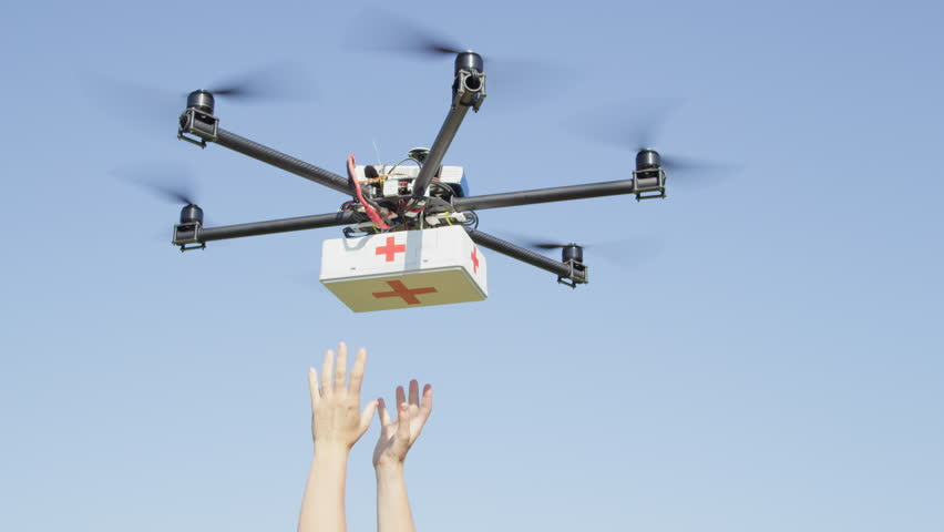 CLOSE UP: UAV aerial drone delivery. Multicopter flying with first aid medicine package. Person' arms getting first aid package box off a delivery drone. Medical air shipment by first responder drone