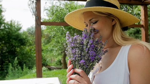 Closeup slow motion video of beautiful woman receiving bunch of lavender flowers in gift box and smelling them