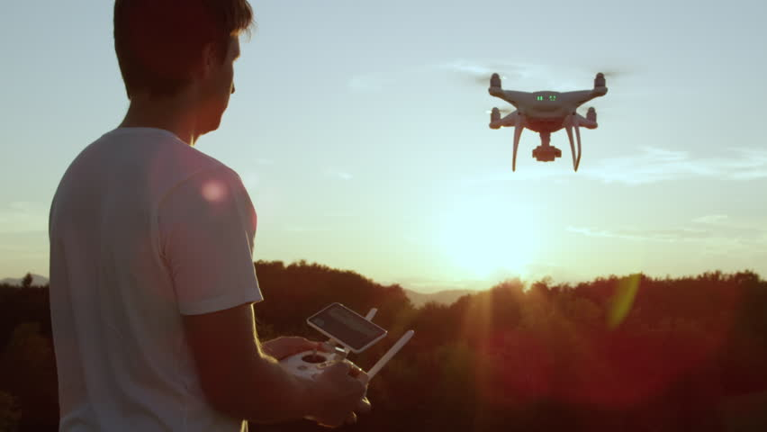 SLOW MOTION CLOSE UP LENS FLARE: Young man flying quadro drone with modern white RC transmitter. Male filmer controlling drone over RC radio controller. Man flying and filming with drone camera