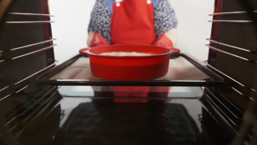 Making homemade apple pie baked in the oven. Sweet dessert recipe Charlotte is easy and quick to make. Granny places baking sheet with apple cake into the oven. Woman uses silicone pan baking mold
