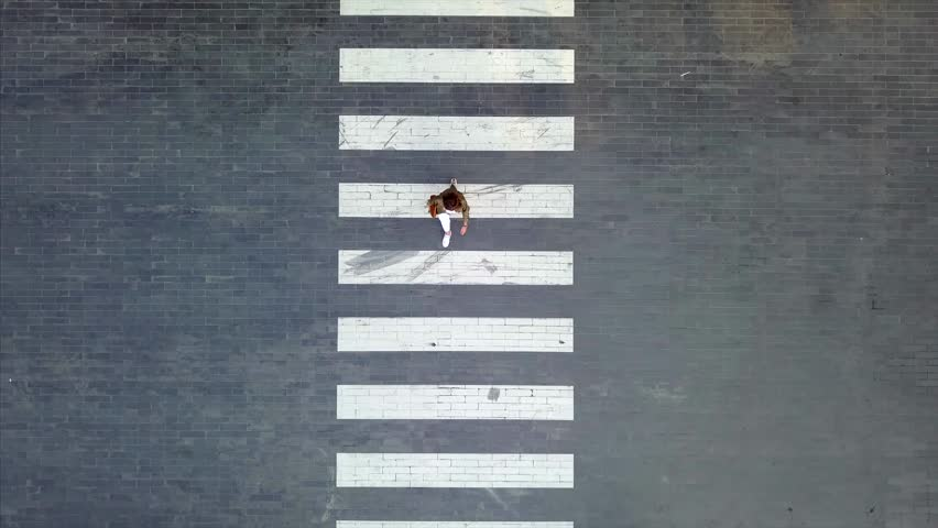 A woman crossing on crosswalk during evening day - Aerial Shot - Birdeyes angle | Shutterstock HD Video #31908439