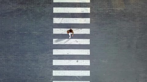A woman crossing on crosswalk during evening day - Aerial Shot - Birdeyes angle