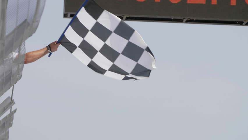 Man holding and waving Checkered race flag in slow motion at finish line on a raceway.  | Shutterstock HD Video #31921819