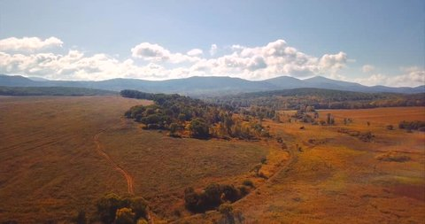 Aerial view of autumn fields and forests, beautiful landscape. Great hills and mountains are on the background. Russia