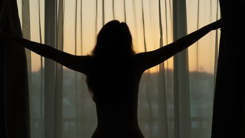Woman open curtains at early morning, black silhouetted half-length shot from back against window. Neat sky colour before sunrise seen through transparent fabric