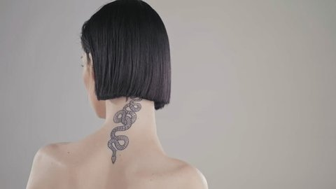Stunning fashion model sensual and cool with a stylish snake tattoo on her neck . Close up in studio with professional makeup and lighting beauty skin care.