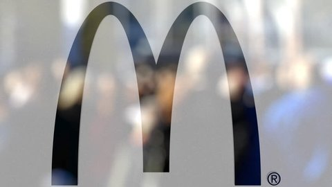 McDonald''s logo on a glass against blurred crowd on the steet. Editorial 3D animation