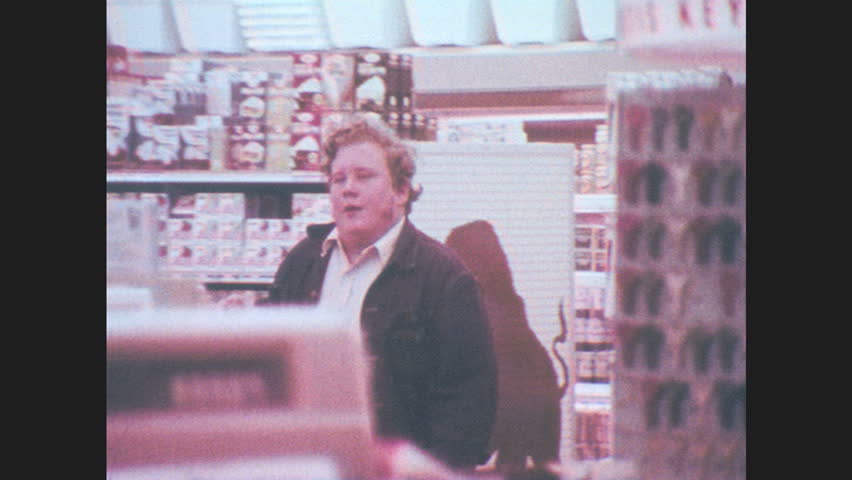 1970s: Teenager sets money on check out counter, points to beer, smiles, walks out of store. Boy runs to car, clerk chases boy. Teenager puts beer on counter, hides face from clerk under cowboy hat.