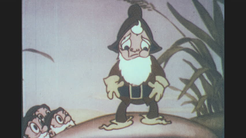 1930s: Dwarf stands on mushroom and addresses group of dwarves. Dwarf asks for support and all dwarves shake their heads yes. Beardless dwarf approaches the mushroom and interrupts.