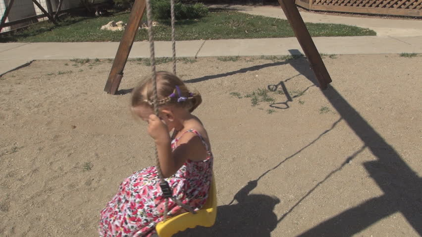 Child Swinging on a Swing Set in a Playground, Little Girl Playing in Park