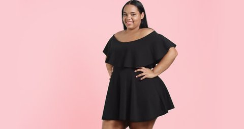 Dancing beautiful young plus size model in black short dress with ruffles isolated on colorful background