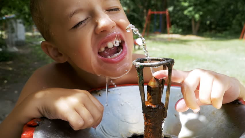 Happy Child Boy Funny Drinking Water from a Drinking Fountain on the Playground. Slow Motion in 96 fps. Close-up of a face and teeth of an eight year old boy. A stream of water pours down on his face