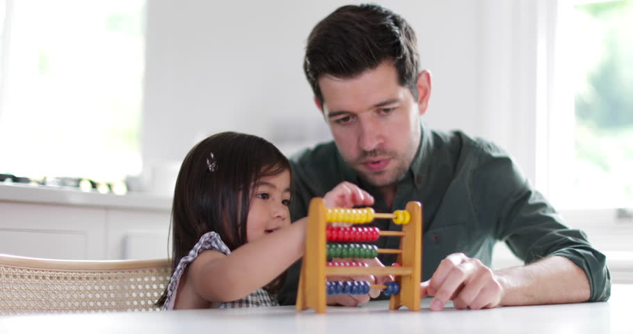 Girl using abacus to count with Father
