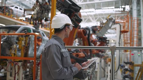 Automobile plant, modern production of cars, robot equipment, working man checks data on the tablet.