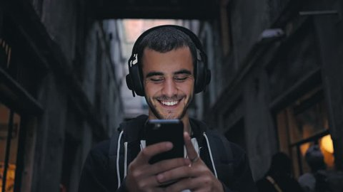 Smiling and laughing handsome young man listening music from his smartphone in wireless black headphones, dancing on street of old town center in europe at twilight or evening time