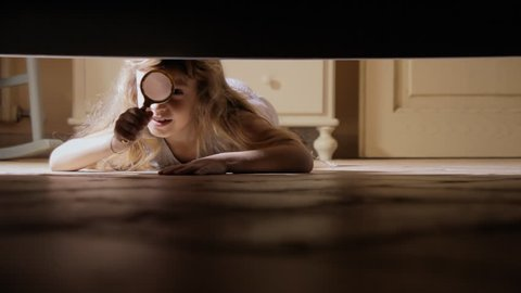 A little girl spying under the bed with a magnifying lens glass.