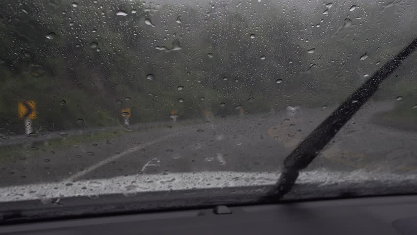 Pov car on mountain Rain splatters car windshield during storm, difficult driving conditions at Khao Kho Phetchabun.