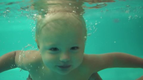 Cute blonde toddler is swimming under the water in the swimming pool until his mother helps him to get out. An underwater shot