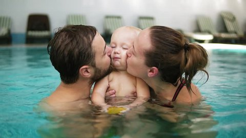 Young mother and father are holding their cute child in their hands in the swimming pool and kissing him from both sides. Happy child is smiling