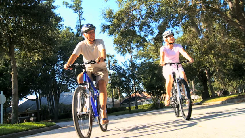 Mature couple wearing safety helmets keeping fit riding their bicycles outdoors on suburban roads