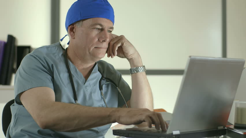 A doctor or surgeon sitting in front of a laptop shows fatigue as he removes his stethoscope and cap as if calling it a day.
