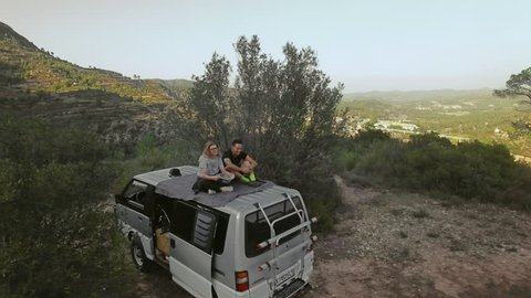 Couple of hipster millennial adventurers explore natural attractions, sit on top of van enjoy view over sunset countryside and mountain, relationship goals of blogger life and travelling