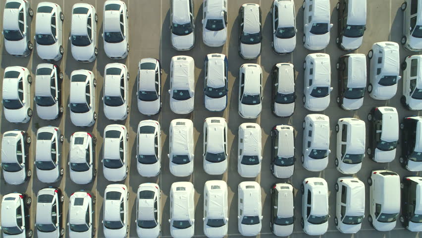 AERIAL TOP DOWN: Flying over big industrial zone with big parking lot of brand new cars. Many white cars waiting for sale and transportation at big sea port parking space. Heavy automobile industry. | Shutterstock HD Video #32093119
