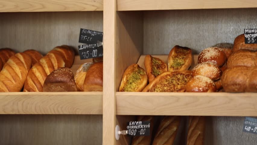 Bakery products on wooden shelves. Inscriptions in Russian - product names. Slow motion