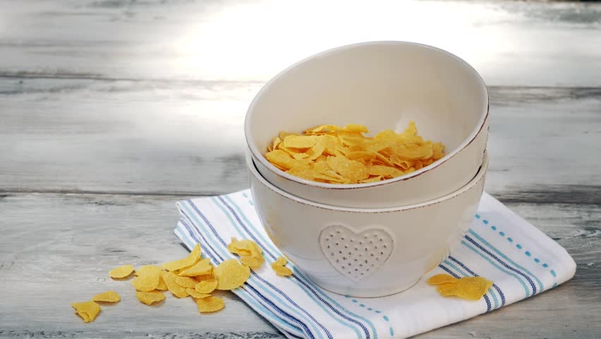Pouring corn flakes to bowl on wooden table. Delicious cornflakes falling into a bowl. Rustic, white wood, healthy breakfast.