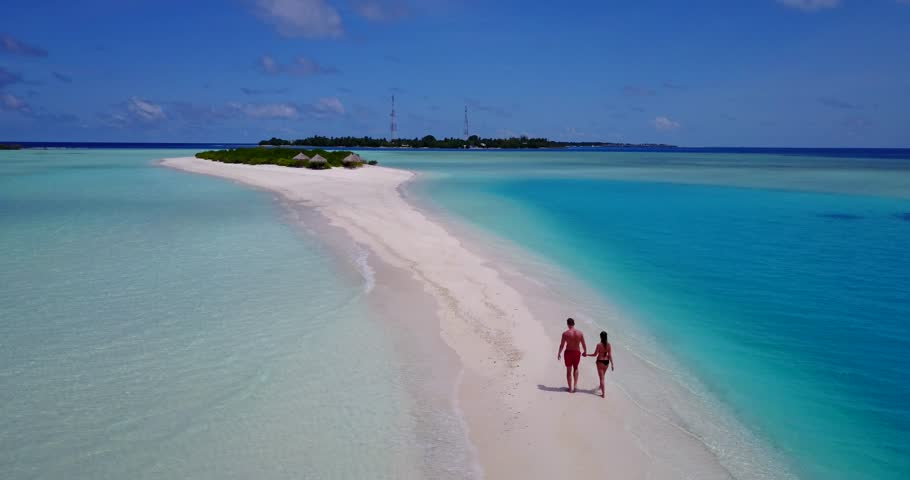 v09062 Two 2 people romantic young people couple walking holding hands with drone aerial flying view on a tropical island of white sand beach and blue sky and sea