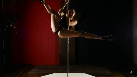 A very long-legged girl is dancing sexually near the pylon. Pole Dance in all its glory.
