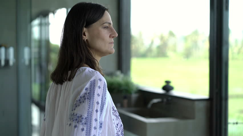 Attractive woman walking to the window and smiling to the camera, close up, steadycam shot  | Shutterstock HD Video #32170309