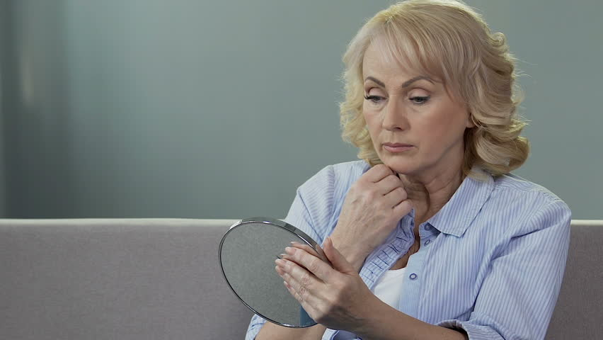 Worried senior woman looking at her reflection in mirror, plastic surgery, aging