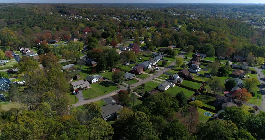 A daytime forward aerial establishing shot of a typical western Pennsylvania residential neighborhood in the early autumn.  Pittsburgh suburbs.