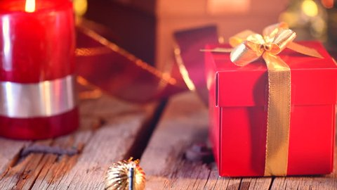 Christmas Gift. Christmas and New Year red gift box close up near decorated christmas tree. Xmas baubles on wooden background. Abstract Blurred Bokeh Background. New Year decoration. 4K UHD video