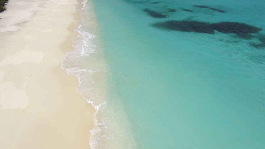 flying over sandy beach, waves and tropical lagoon