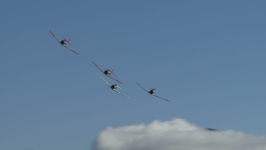 Four ship T6 Harvards in formation flight with exhaust vapour trail