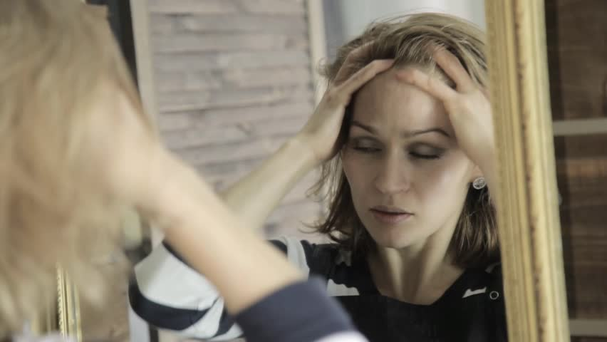 Beautiful woman massages her head in front of mirror with closing his eyes | Shutterstock HD Video #32229919