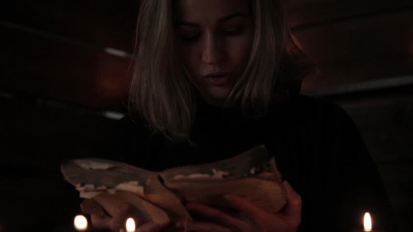 Charlatan witch reading book of black magic, view on burning candle. magic ritual | Shutterstock HD Video #32230450