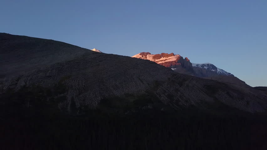 Aerial shot of Rocky Mountains peaks with snow while sunrise light