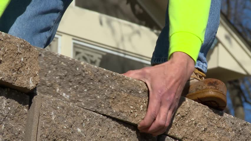 Stone masons install a rock wall at a residence with skill and care. The rocks are gently placed upon each other without mortar or cement. Their hands are hardened from years of labor. | Shutterstock HD Video #32238229