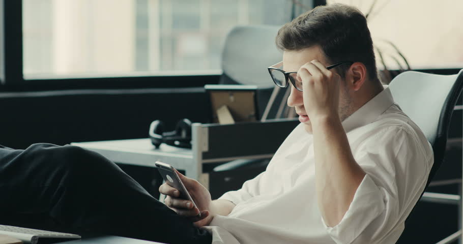 Attractive man in glasses sitting at a desk uses a telephone in the office phone mobile technology modern smartphone male online talk happy tablet business communication Slow Motion Shot | Shutterstock HD Video #32245789